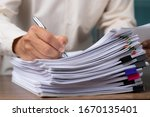 Small photo of Male office workers with yellow shirt holding and writing documents on office desk, Stack of business overload paper.