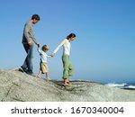 Family on vacation walking on rocky beach overlooking Atlantic Ocean