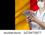 doctor with a stethoscope holds euro banknotes in the background of the silk national flag of Belgium, the concept of medical insurance, budget, cost of treatment, organ donation