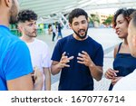 Young mix raced man telling exciting funny story to his friends. Multiethnic men and women standing at city construction, talking, listening. Friendship concept