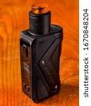Small photo of Usti nad Labem / Czech republic - 3.12.2020: Black vaping squonk mod GeekVape Aegis Squonk on brown wooden table - modern e-cig device.