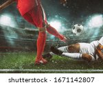 Small photo of Soccer scene at the stadium with player in a red uniform kicking the ball and opponent in tackle to defend
