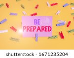 Small photo of Handwriting text writing Be Prepared. Concept meaning To make ready beforehand for a specific purpose as for an event Colored clothespin papers empty reminder yellow floor background office.