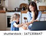 Small photo of Working mom works from home office with kid. Woman and cute child using laptop. Freelancer workplace in cozy kitchen. Happy mother and daughter. Female business, empathy, care. Lifestyle family moment