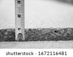 Small photo of Frost heave crack in residential concrete sidewalk with tape measure