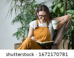 Young female gardener in glasses wearing overalls, resting after work, sitting on wooden chair in home greenhouse, holding reusable foldable coffee/tea mug, smiling and reading book on her knees.  - stock photo