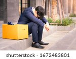 Small photo of Unemployed man, The economic downturn made people unemployed, Desperate businessman sitting hopelessly on stair in central business district due to unemployment. failure, desperation, depression.
