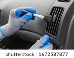 Small photo of Man hands wearing protective gloves using cleaning brush and removing dust from car air conditioning vent grill. Car detailing or valeting concept.