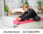 Small photo of Fitness training online, senior woman at home with laptop.