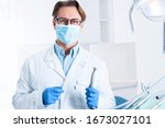 Small photo of Man in white doctor robe uniform, glasses, mask, gloves is holding instrument, standing in office, clinic. Dentist workplace. Orthodontist is preparing for visit of patient. Dentistry concept.