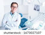 Small photo of Portrait of smiling man in white doctor robe uniform is standing in office, clinic with chair, instruments. Dentist workplace. Orthodontist is preparing for visit of patient. Dentistry concept.
