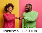Small photo of Positive dark skinned young woman and man bump fists, agree to be one team, look happily at each other, celebrates completed task, wear pink and green clothes, pose indoor, have successful deal