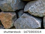Small photo of Rough uncouth granite cobbles. Granite stones stacked one on one. Large pieces of raw granite. Abstract background. Selective focus. Close-up.