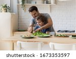 Small photo of Caring young father show teach little preschooler son chop vegetables prepare healthy diet salad, smiling loving dad learn cooking with small boy child, making lunch on weekend in kitchen together