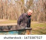 A Mature Man Near A Trash Can...