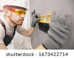 Electrician install switches and sockets checks tool levelness at home. - stock photo