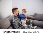 Brave soldier sitting on sofa with his beloved son and playing with him. - stock photo
