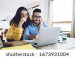 Small photo of Cheerful man and woman with pencil in had near face smiling while planning further work together and using laptop at home