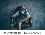 Small photo of Masculine confident old man shareholder sit chair relax hold glass brandy smoke cigarette look wear white shirt brown luxury pants green socks isolated grey concrete wall color background