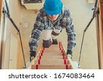 Construction Worker Walking Upstairs To Take a Look at House Attic. Wooden Second Level Stairs. - stock photo