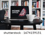 Small photo of Home office theme. Home office during coronavirus pandemic. Novel coronavirus 2019 COVID-19 theme. Coronavirus wallpaper on computer. Coffee Cup in foreground.