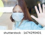 Small photo of portrait of a red-haired girl through the window in a protective face mask as a concept of quarantine and isolation due to the covid-19 coronavirus, border closure and social disunity in pandemic