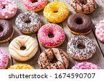 Small photo of assorted donuts with chocolate frosted, pink glazed and sprinkles . Top view