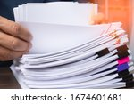 Small photo of Business man hand pick up Stack overload document report paper with colorful paperclip, business and paperless concept.