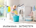 Small photo of Child in laundry room with washing machine or tumble dryer. Kid helping with family chores. Modern household devices and washing detergent in white sunny home. Clean washed clothes on drying rack.