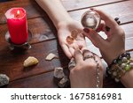 Small photo of A fortune teller predicts the fate of love with wedding rings, a magic ball, lighted candles and magic stones. A Gypsy woman performs a love spell. A clairvoyant palmist reads by hand with a candle.