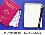 Small photo of Istanbul, Turkey - March 18, 2020: Surface Passport of Turkey, Turkish identity card, Driving Licence of Turkey and blank notebook paper with a pen on blue background.