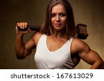 Young woman bodybuilder with hammer. - stock photo