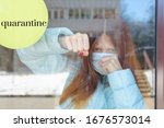 """Small photo of portrait of a red-haired girl behind glass in a protective face mask as a concept of quarantine and isolation due to the covid-19 coronavirus, border closure and social disunity, text """"quarantine"""""""