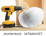 a yellow battery operated drill with screwdriver bit and a hard hat in a residential construction setting isolated on whit - stock photo