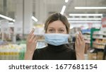 Small photo of A young woman puts on a medical mask in a grocery supermarket close-up and looks at the camera, protection from coronavirus, shopping in a store to wait out the quarantine.