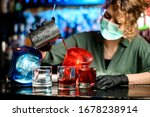 Small photo of Young bartender girl in medical mask and black gloves accurate pour drink from steel glass into glasses with ice. Blue and red warning lights inform about quarantine.