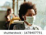 Small photo of Thoughtful black businesswoman wearing face mask for virus protection and looking through the window while traveling by public transportation.
