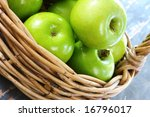 Cane basket of granny smith apples, on rustic wooden table. - stock photo