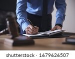 Male Lawyer Working At Table In ...