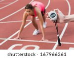 Small photo of Close-up of a hand timing a blurred young woman's run on the running track