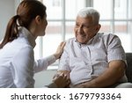Small photo of Caring nurse talks to old patient holds his hand sit in living room at homecare visit provide psychological support listen complains showing empathy encouraging. Geriatrics medicine caregiving concept