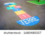 """Small photo of A multicolored hopscotch painted on the asphalted ground of a french schoolyard. The word """"Terre"""" at the start of the hopscotch means """"Earth"""" and the word """"Ciel"""" at the top means """"Heaven""""."""