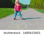 Little Girl Playing Hopscotch...