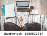 Small photo of Businesswoman dressed pajamas writing day plan enjoying morning coffee on living room floor office with laptop, papers and other stuff top view shot.Distance work in worldwide quarantine time concept