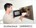 man heating food in microwave | Shutterstock . vector #168084011