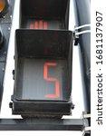 Small photo of Black metallic semaphore. Red number 5 light in semaphore