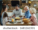 Small photo of Happy extended family talking while having lunch together in dining room. Focus is on young man.