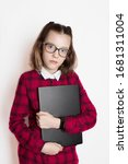 girl child wiseacre excellent pupil in glasses, in a red plaid shirt dress outfit and with a laptop in her hands