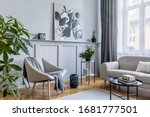 Small photo of Stylish scandinavian home interior of living room with design gray sofa, armchair, marble stool, black coffee table, modern paintings, decoration, plant and elegant personal accessories in home decor.