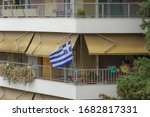Greek flag waving on balcony for a national celebration. Blue and white Greek flag with cross outside city homes, celebrating the March 25 1821 day of Greek War of Independence.